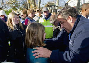 Photo -   New Jersey Gov. Chris Christie gives little 9-year-old Ginjer Doherty a pep talk outside the Port Monmouth fire station in Port Monmouth, N.J., where he visited residents and first responders Monday, Nov. 5, 2012 a week after Hurricane Sandy devasted New Jersey. At left, wiping her eye, is Ginjer's mom, Gail. (AP Photo/The Philadelphia Inquirer, Clem Murray, Pool)