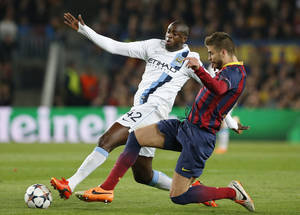 Photo - Manchester City's Yaya Toure, left is tackled by Barcelona's Gerard Pique during a Champions League, round of 16, second leg, soccer match between FC Barcelona and Manchester City at the Camp Nou Stadium in Barcelona, Spain, Wednesday March 12, 2014. (AP Photo/Emilio Morenatti)