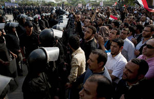 "photo - Supporters of Egyptian President Mohammed Morsi chant slogans as riot police, left, stand guard in front of the entrance of Egypt's top court, in Cairo, Egypt, Sunday, Dec. 2, 2012. Egypt's top court announced on Sunday the suspension of its work indefinitely to protest ""psychological and physical pressures,"" saying its judges could not enter its Nile-side building because of the Islamist president's supporters gathered outside. (AP Photo/Nasser Nasser)"