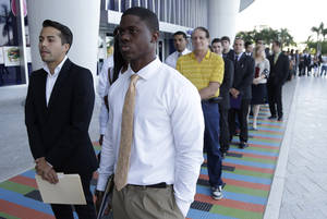 Photo -  In this Oct. 23, 2013, file photo, Luis Mendez, 23, left, a student at Miami Dade College, and Maurice Mike, 23, a student at Florida International University, wait in line at a job fair held by the Miami Marlins at Marlins Park in Miami, Fla. The job market for new college graduates is brightening but remains weaker than before the Great Recession began. AP Photo  <strong>Lynne Sladky -   </strong>