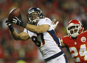 Photo - FILE - In this Dec. 1, 2013 file photo, Denver Broncos wide receiver Eric Decker (87) makes a touchdown reception against Kansas City Chiefs cornerback Brandon Flowers (24) during the second half of an NFL football game in Kansas City, Mo. Where will Maurice Jones-Drew, Decker and Michael Vick wind up. They are some of the best-known players available as NFL free agency begins. (AP Photo/Ed Zurga, File)
