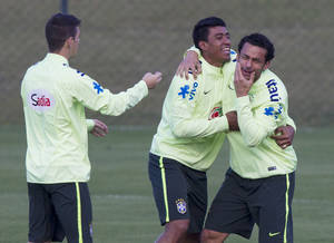 Photo - Brazil's soccer players, Fred, right, Paulinho, center and Oscar, joke around during a practice session at the Granja Comary training center, in Teresopolis, Brazil, Sunday, July 6, 2014. Brazil will face Germany on Tuesday in their World Cup semifinals' match, without superstar soccer player Neymar. (AP Photo/Leo Correa)