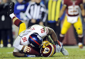 Photo - Washington Redskins quarterback Robert Griffin III (10) is sacked by New York Giants defensive end Justin Tuck (91) during the second half of an NFL football game Sunday, Dec. 1, 2013, in Landover, Md. The Giants won 24-17. (AP Photo/Nick Wass)