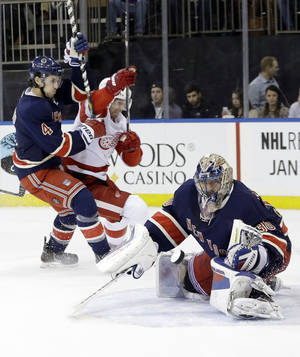 Photo - New York Rangers goalie Henrik Lundqvist (30), of Sweden, stops a shot on the goal as Detroit Red Wings' Mikael Samuelsson and Michael Del Zotto (4) fight for position during the first period of an NHL hockey game, Thursday, Jan. 16, 2014, in New York. (AP Photo/Frank Franklin II)