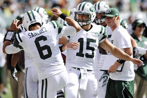 Photo -   New York Jets quarterbacks Mark Sanchez, left, and Tim Tebow celebrate after a touchdown during the second half of an NFL football game against the Buffalo Bills at MetLife Stadium, Sunday, Sept. 9, 2012, in East Rutherford, N.J. (AP Photo/Bill Kostroun)