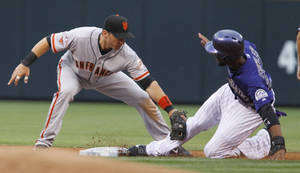 Photo - San Francisco Giants' Marco Scutaro, left, tags out Colorado Rockies' Dexter Fowler, right, as he tries to steal second during the first inning of a baseball game, Monday, Aug. 26, 2013, in Denver. Fowler left the game after the play. (AP Photo/Barry Gutierrez)
