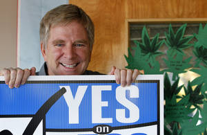 "Photo - In this Monday, Nov. 26, 2012 photo, travel guide author and marijuana legalization supporter Rick Steves holds a campaign sign in his office in Edmonds, Wash next to a door covered with marijuana leaf-shaped notes from his staff congratulating him on the passage of a referendum legalizing marijuana in the state. In the late-1980s heyday of the ""Just Say No"" campaign, a man calling himself ""Jerry"" appeared on a Seattle radio station's midday talk show, using a pseudonym because he was a businessman, afraid of what his customers would think if they heard him criticizing U.S. marijuana laws. A quarter century later, ""Jerry"" had no problem using his real name - Rick Steves - as one of the main forces behind Washington's successful ballot measure to legalize, regulate and tax marijuana for adults over 21. (AP Photo/Elaine Thompson)"