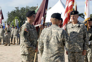 photo - Maj. Gen. Bryan R. Kelly, left, prepares to pass the Army Reserve Medical Command colors to Command Sgt. Maj. Harold P. Estabrooks, right, as Maj. Gen. Luis R. Visot, deputy commanding general, operations of the U.S. Army Reserve Command, looks on during the change of command ceremony. Photo provided by U.S. Army