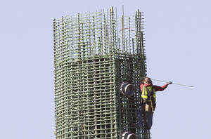 photo - A worker reinforces rebar Friday on a tower on a light rail bridge construction project over the Willamette River in Portland, Ore.  AP Photo