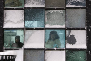 Photo - Riders wait in a bus stop where color-tinted windows collect snow during a storm, Friday, Feb. 8, 2013, in Portland, Maine. The National Weather Service says a blizzard warning is issued Friday evening for the southern coast. The forecast calls for up to 2 feet of snow and winds gusting to 50 mph.(AP Photo/Robert F. Bukaty)