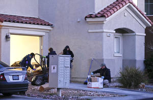 "Photo - FBI agents gather outside a Las Vegas home owned by former Los Angeles police officer Christopher Dorner while collecting evidence, Thursday, Feb. 7, 2013. Thousands of police officers hunted Thursday for one of their own: a former Los Angeles officer angry over his firing and sought in a deadly shooting rampage after warning he would wage ""warfare"" on those who wronged him, authorities said. (AP Photo/Julie Jacobson)"