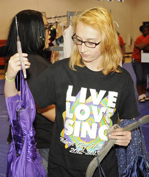 Photo - Caroline Brown, from Midwest City High School, chooses a couple of dresses to try on during a prom dress giveaway. Bound 4 Glory and Beyond partnered with the Boys and Girls Club of Oklahoma County to donate the dresses.  Photo by M. Tim Blake, For The Oklahoman