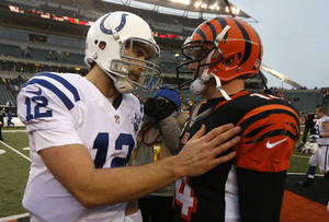 Photo - Indianapolis Colts quarterback Andrew Luck (12) meets with Cincinnati Bengals quarterback Andy Dalton (14) after the Bengals defeated the Colts 42-28 in an NFL football game, Sunday, Dec. 8, 2013, in Cincinnati. (AP Photo/David Kohl)
