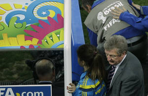 Photo - England's manager Roy Hodgson, bottom right corner, leaves the pitch after losing 1-2 to Uruguay during the group D World Cup soccer match between Uruguay and England at the Itaquerao Stadium in Sao Paulo, Brazil, Thursday, June 19, 2014.  (AP Photo/Michael Sohn)