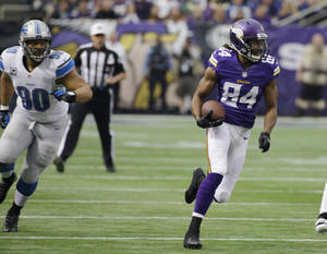Photo - Minnesota Vikings wide receiver Cordarrelle Patterson runs from Detroit Lions defensive tackle Ndamukong Suh, left, during a 50-yard touchdown run in the first half of an NFL football game, Sunday, Dec. 29, 2013, in Minneapolis. (AP Photo/Ann Heisenfelt)