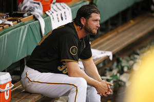 Photo - Pittsburgh Pirates relief pitcher Jason Grilli sits in the dugout after giving up a solo home run to Cincinnati Reds' Devin Mesoraco during the ninth inning of a baseball game in Pittsburgh, Thursday, June 19, 2014. The Pirates won 4-3 in 12 innings. (AP Photo/Gene J. Puskar)