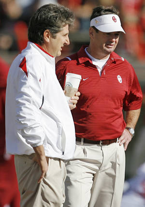 Photo - Texas Tech head coach Mike Leach, left, and Oklahoma head coach Bob Stoops talk before the college football game between the University of Oklahoma Sooners (OU) and the Texas Tech University Red Raiders (TTU) at Jones AT&T Stadium in Lubbock, Texas, Saturday, Nov. 21, 2009. Photo by Nate Billings, The Oklahoman
