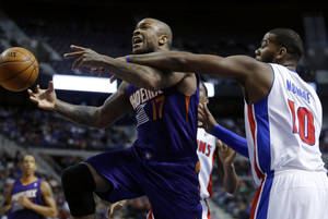 Photo - Phoenix Suns forward P.J. Tucker (17) is fouled by Detroit Pistons center Greg Monroe (10) while driving to the basket during the first half of an NBA basketball game, Saturday, Jan. 11, 2014, in Auburn Hills, Mich. (AP Photo/Duane Burleson)