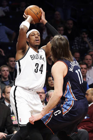 Photo - Brooklyn Nets forward Paul Pierce (34) looks to pass over Josh McRoberts in the first half of an NBA basketball game Wednesday, Feb. 12, 2014, in New York. (AP Photo/John Minchillo)