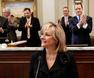 Photo - Gov. Mary Fallin receives sustained applause as she prepares to deliver her 2012 State of the State address to a joint session of the Oklahoma legislature in the House Chamber on the opening day of the session, Monday, Feb, 6, 2012.  Behind Fallin, to the right, is Lt. Gov. Todd Lamb.  Photo by Jim Beckel, The Oklahoman