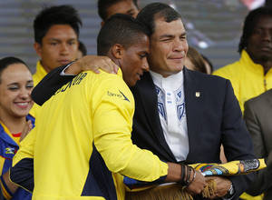 Photo - President Rafael Correa, right, hands the national flag to Antonio Valencia, captain of Ecuadorian nationasl soccer team during a farewell ceremony in Quito, Ecuador, Monday, May 26, 2014. While Ecuador went undefeated at home, beating every opponent in Quito except Argentina, with whom they drew, it failed to win on the road drawing just three times. Even so World Cup Fever has gripped the country with Ecuadorians excited about their squad's third appearance in the tournament. (AP Photo/Dolores Ochoa)