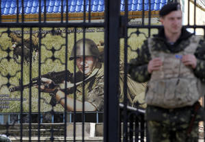 Photo - A Ukrainian soldier stands guard at the gate of a military base in the port of Kerch, Ukraine, Monday, March 3, 2014. Pro-Russian troops controlled a ferry terminal on the easternmost tip of Ukraine's Crimea region close to Russia on Monday, intensifying fears that Moscow will send even more troops into the strategic Black Sea region in its tense dispute with its Slavic neighbor. (AP Photo/Darko Vojinovic)