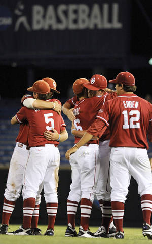 Photo - Oklahoma players console each other after the Sooners' 3-2 loss to South Carolina on Thursday. AP PHOTO
