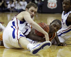 Photo - Kansas guard Brady Morningstar, left, and Texas guard/forward Jordan Hamilton (3) battle for the ball during the second half of an NCAA college basketball game for the championship of the Big 12 men's basketball tournament on Saturday, March 12, 2011, in Kansas City, Mo. (AP Photo/Charlie Riedel)