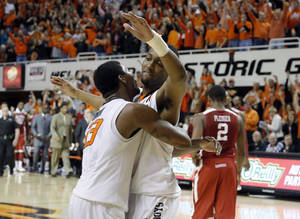 Photo - Oklahoma State's Marcus Smart (33) and Brian Williams (4)  celebrate in front of Oklahoma's Steven Pledger (2) at the end ofthe Bedlam men's college basketball game between the Oklahoma State University Cowboys and the University of Oklahoma Sooners at Gallagher-Iba Arena in Stillwater, Okla., Saturday, Feb. 16, 2013. Photo by Sarah Phipps, The Oklahoman