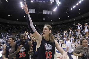 Photo - Gonzaga's Kelly Olynyk (13) and teammate Sam Dower (35) celebrate their 70-65 victory over Brigham Young during their NCAA basketball college game Thursday, Feb. 28, 2013, in Provo, Utah.  (AP Photo/Rick Bowmer) ORG XMIT: UTRB113