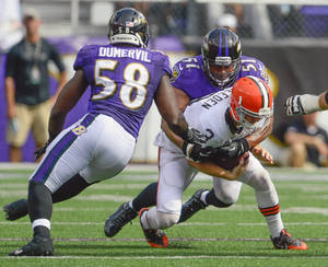 Photo - Baltimore Ravens inside linebacker Daryl Smith records a sack on Cleveland Browns quarterback Brandon Weeden as teammate Elvis Dumervil lends an assist during the second half of their game on Sunday, September 15, 2013, in Baltimore, Maryland. (Doug Kapustin/MCT) ORG XMIT: 1143252