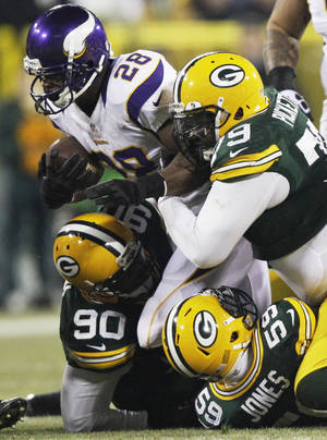 Photo - Minnesota Vikings running back Adrian Peterson (28) is taken down by Green Bay Packers nose tackle B.J. Raji (90), inside linebacker Brad Jones (59) and defensive end Ryan Pickett (79) during the first half of an NFL wild card playoff football game Saturday, Jan. 5, 2013, in Green Bay, Wis. (AP Photo/Kiichiro Sato)