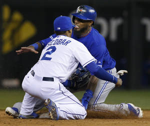 Photo - Toronto Blue Jays' Jose Reyes, back, injures his leg while beating the tag by Kansas City Royals shortstop Alcides Escobar (2) during the sixth inning of a baseball game at Kauffman Stadium in Kansas City, Mo., Friday, April 12, 2013. (AP Photo/Orlin Wagner)