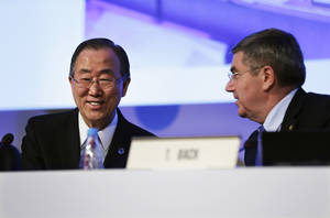Photo - United Nations Secretary-General Ban Ki-moon, left, sits next to International Olympic Committee President Thomas Bach after Ban addressed the IOC general assembly ahead of the upcoming 2014 Winter Olympics, Thursday, Feb. 6, 2014, in Sochi, Russia. It was the first time a U.N. secretary-general delivered a keynote address to the IOC's general assembly. (AP Photo/David Goldman)
