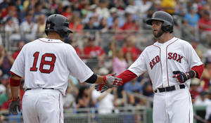 Photo - Boston Red Sox's Dustin Pedroia,right, is greeted by Shane Victorino (18) after both scored on a two-run double by Mike Napoli during the third inning of an exhibition baseball game against the Minnesota Twins in Fort Myers, Fla., Saturday, March 29, 2014. (AP Photo/Gerald Herbert)
