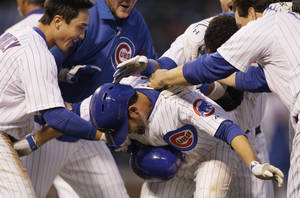 Photo -   Chicago Cubs' David DeJesus, center, celebrates with teammates after he walked to first base during the 11th inning of a baseball game against the Los Angeles Dodgers in Chicago, Sunday, May 6, 2012. The Cubs won 4-3. (AP Photo/Nam Y. Huh)