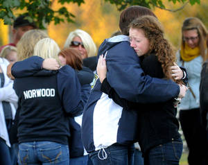 Photo - Savannah Walker, right, hugs Alex James during a candlelight vigil in honor of Richard Michael Ridgell at Jaycee Park in Westminster, Md. Tuesday, Sept. 17, 2013.  Ridgell was killed in Monday's shooting at the Navy Yard in Washington. (AP Photo/Carroll County Times, Dave Munch)