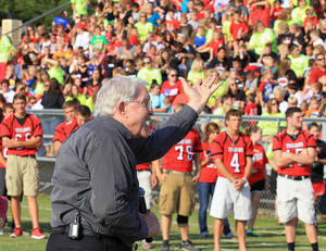 Photo - Former Baylor head football coach Grant Teaff addresses the West Trojan football players, background, and the community on Thursday, Aug.  29, 2013, at a morning pep rally in West, Texas.  The West Trojans open the season Thursday night on their field that was used as a triage site when West Fertilizer Plant exploded on April 17, where 15 people died. (AP Photo/ Waco Tribune Herald, Jerry Larson)