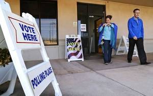 """Photo - Jessi Riesenberg places an """"I Voted"""" sticker on her shirt as she and Cary Pirrong leave the Oklahoma County Election Board office after voting on Thursday, Feb. 27, 2014.  Photo by Jim Beckel, The Oklahoman"""