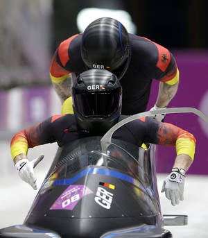 Photo - The team from Germany GER-2, piloted by Thomas Florschuetz and brakeman Kevin Kuske, start their third run during the men's two-man bobsled competition at the 2014 Winter Olympics, Monday, Feb. 17, 2014, in Krasnaya Polyana, Russia. (AP Photo/Michael Sohn)
