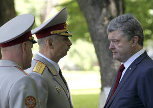 Photo - Ukrainian President Petro Poroshenko, right, meets with acting Ukrainian Defense Minister Mykhailo Koval, center, in Kiev, Ukraine, Wednesday, June 18, 2014.  Ukraine's president said Wednesday that government forces will unilaterally cease fire to allow pro-Russian separatists in the east of the country a chance to lay down weapons or leave the country, a potential major development to bring peace to the country. (AP Photo/Mykhailo Markiv, pool)