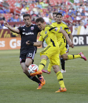 Photo - RETRANSMISSION TO CORRECT YEAR - Columbus Crew's Ethan Finlay, right, kicks the ball as D.C. United's Steven Birnbaum (15) defends during the first half of an MLS soccer game, Saturday, June 7, 2014, in Landover, Md. (AP Photo/Luis M. Alvarez)