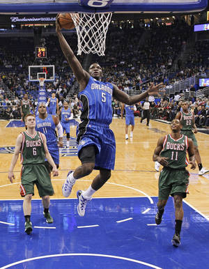 Photo - Orlando Magic's Victor Oladipo (5) makes a basket as he gets out in front of Milwaukee Bucks' Nate Wolters (6) and Brandon Knight (11) during the first half of an NBA basketball game in Orlando, Fla., Friday, Jan. 31, 2014. (AP Photo/John Raoux)