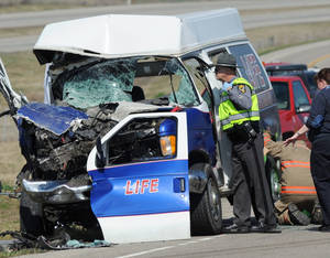 Photo -   Ohio Highway Patrol investigates the scene of a fatal two-vehicle crash on Hospital Road at the intersection of Delano Road near Chillicothe, Ohio, Wednesday, March 14, 2012. The driver and passenger of the ambulance died in the crash. (AP Photo/Chillicothe Gazette, Frank Robertson)