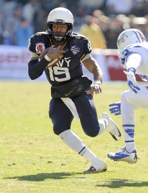Photo - Navy Midshipmen quarterback Keenan Reynolds (19) runs upfield past Middle Tennessee Blue Raiders defensive end Raynard Felton (43) in the first half during the Armed Forces Bowl NCAA college football game, Monday, Dec. 30, 2013, in Fort Worth, texas. (AP Photo/Matt Strasen)