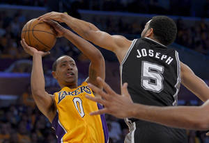 Photo - San Antonio Spurs guard Cory Joseph, right, blocks a shot by Los Angeles Lakers guard Andrew Goudelock during the second half in Game 3 of a first-round NBA basketball playoff series, Friday, April 26, 2013, in Los Angeles. (AP Photo/Mark J. Terrill)
