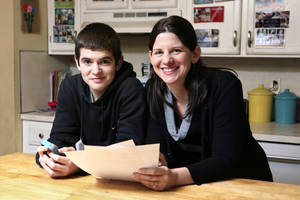 Photo - In this Jan. 4, 2013, photo, Janell Burley Hofmann, right, poses with her son Gregory at their home in Sandwich, Mass. Janell holds a copy of the contract she drafted and that Gregory signed as a condition for receiving his first Apple iPhone. (AP Photo/Michael Dwyer)