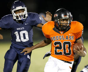 photo - Aliston Cobb of Douglass runs past Star Spencer's Carlos Hutson during the finals of the All-City Athletic Conference Football Preview at Moses F. Miller Stadium in Oklahoma City, Friday, August 27, 2010.  Photo by Bryan Terry, The Oklahoman