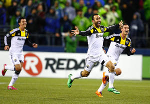 Photo - Columbus Crew players celebrate with Justin Meram, center, after he scored the game-winning goal in stoppage time against SoundersFC at CenturyLink Field on Saturday, March 29, 2014, in Seattle, Wash. Columbus won 2-1. (AP Photo/The Seattle Times, John Lok)