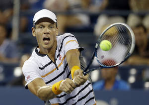 Photo - Tomas Berdych, of the Czech Republic, returns a shot to Dominic Thiem, of Austria, during the fourth round of the 2014 U.S. Open tennis tournament Tuesday, Sept. 2, 2014, in New York. (AP Photo/Darron Cummings)
